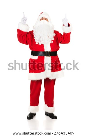 Full length Santa Claus pointing his hands up. - stock photo
