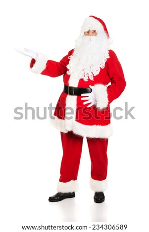 Full length Santa Claus with a welcome gesture. - stock photo