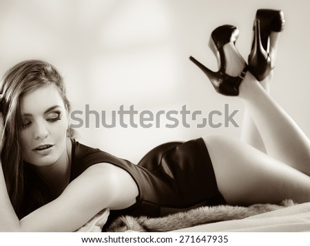 Full length sensual woman in lingerie with long hair lying on carpet in retro vintage high heels shoes black white photo