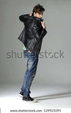 full length serious young man in leather jacket on gray background - stock photo