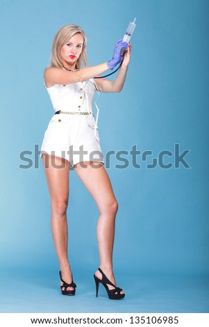 Full length sexual woman in nurse suit with stethoscope and syringe blue background