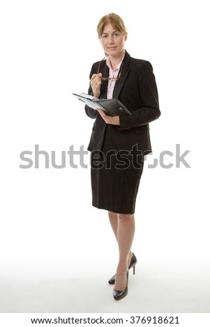 Full length shot of a business woman holding her glasses is writing in her personal organiser isolated on white