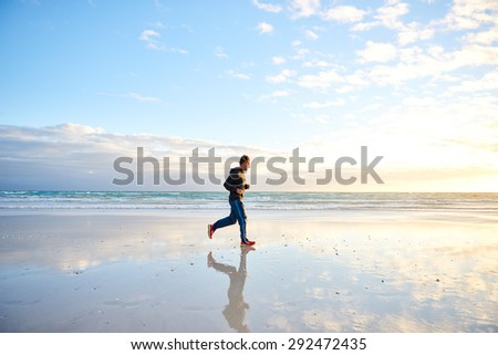 Full length shot of a fit young man running on the beach early in the morning
