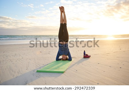 Full length shot of a fit young woman performing a yoga headstand on the beach early in the morning - stock photo