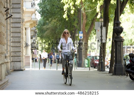 Full length shot of a happy middle aged woman riding bike through the city.