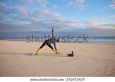 Full length shot of a healthy young woman on her yoga mat performing a pose in the light of early morning sun - stock photo