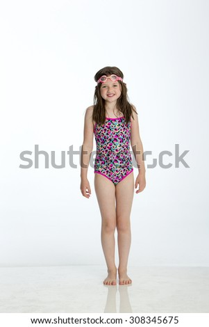 Full length shot of a little girl wearing a swimming costume with goggles on her head. She is smiling at the camera and standing against a white background. - stock photo