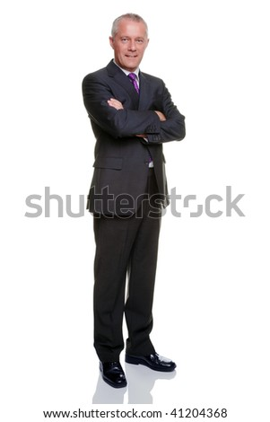 Full length shot of a mature businessman wearing a suit with his arms folded looking at camera. - stock photo