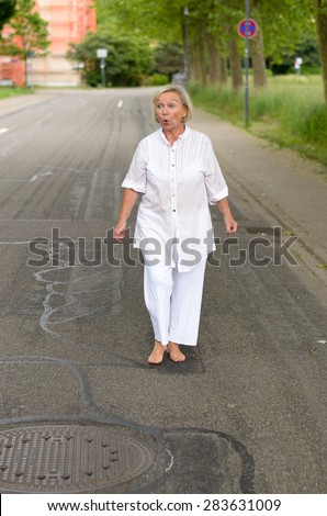 Full Length Shot of a Middle Aged Blond Woman at the Street, Wearing All White Clothes with Bare Feet, Showing Shocked Facial Expression While Looking Into Distance. - stock photo
