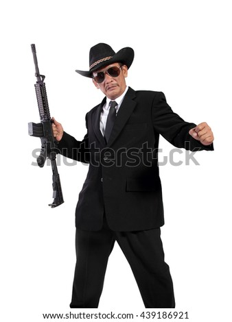 Full length shot of a mobster in black fashionable outfits posing with his weapon, isolated on white background