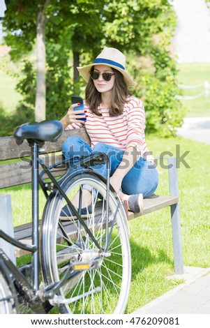 Full length shot of a smiling young woman using her handy while sitting at the park.