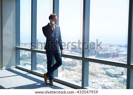Full length shot of a stylish young businessman standing alongside the large windows of a modern office high up on the top floor, using his phone while looking out at the view - stock photo