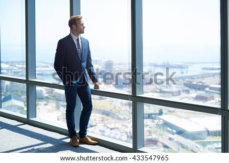 Full length shot of a stylish young businessman wearing a modern suit, who is a high achiever, standing on the top floor of an office building looking out at the view through large windows - stock photo