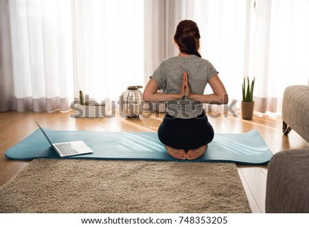 Full length shot of a woman doing yoga at home