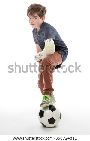 Full length shot of a young boy who cant play football with his friends because he has broken his left arm - stock photo