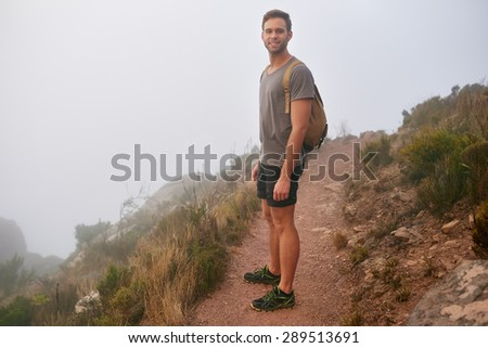 Full length shot of a young male hiker smiling while on a mountain nature trail on a misty morning