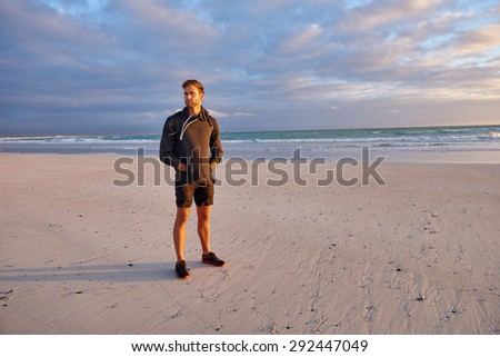 Full length shot of a young man wearing sports wear standing on a beach at sunrise looking fit and healthy