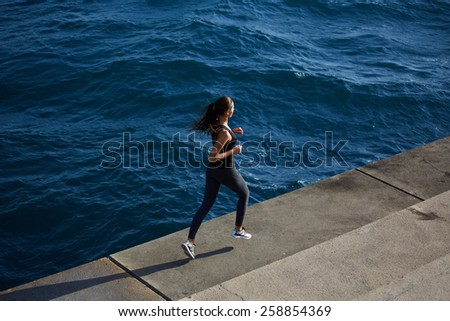 Full length shot of a young woman running along the seashore at sunny day, dynamic picture with sport girl in action running over ocean waves background - stock photo