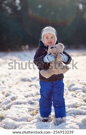 Full length shot of an adorable little boy holding his teddy bear outdoors on a snowy winter's day - stock photo