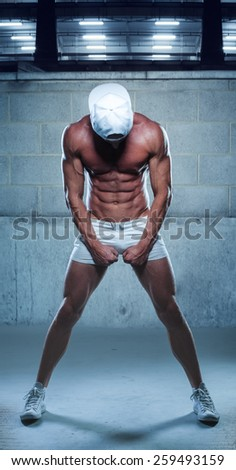 Full Length Shot of an Athletic Young Man in Sexy White Mini Shorts and Cap with Sneakers Facing Down on a Blue Gray Background. - stock photo