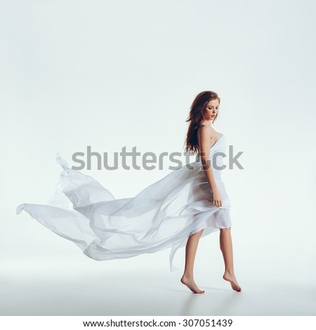 Full length shot of attractive young female model naked on white background. Sensual woman with transparent fabric on her body looking down. - stock photo