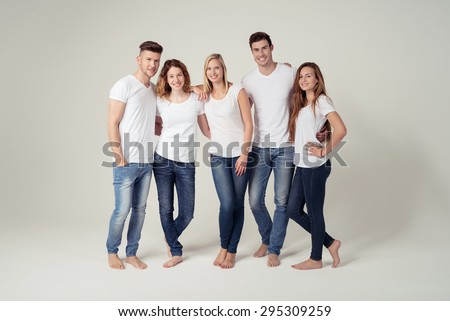 Full Length Shot of Closed Young Friends Smiling at the Camera in Plain White Shirts with Copy Space and Blue Jeans, Captured in Studio on White Background. - stock photo