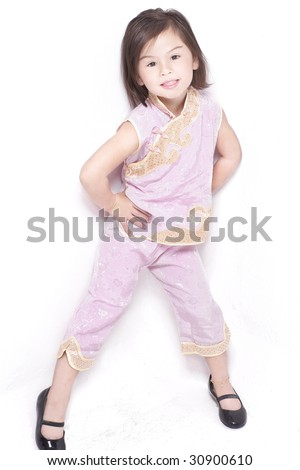 Full-length shot of Eurasian little girl of chinese-english heritage dressed in pink cheongsam, shot against white in studio