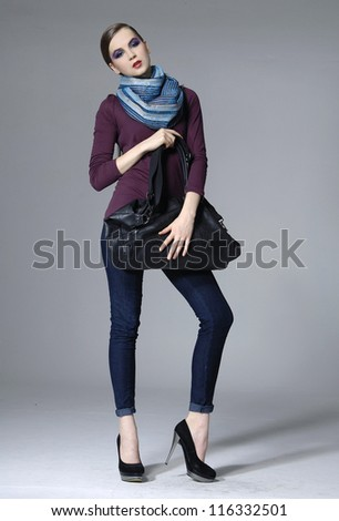full length shot of fashion model in scarf posing on grey background - stock photo