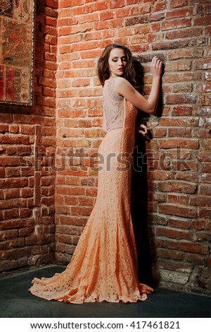 Full length shot of fashionable model girl at peach evening dress background brick wall.