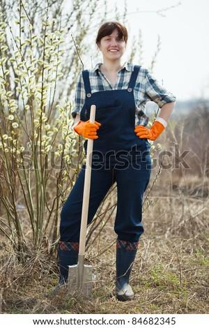 full length shot of female farmer with spade in spring - stock photo