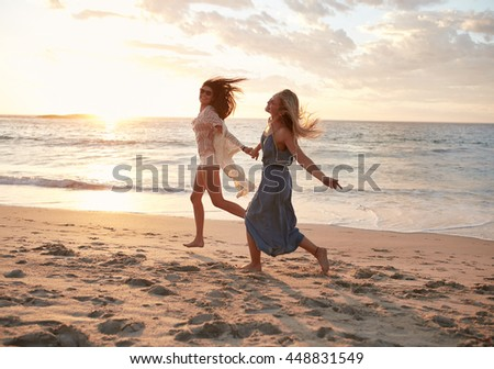 Full length shot of female friends running on the beach and having fun. Female friends enjoying a day on the sea shore. - stock photo