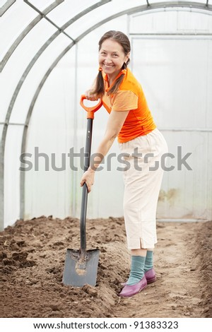 full length shot of female spading  with spade in greenhouse