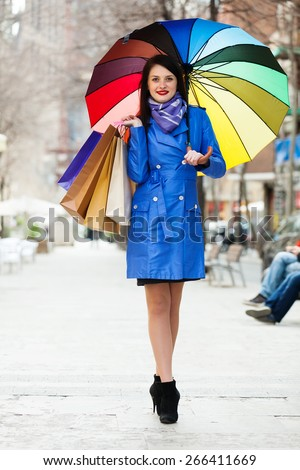full length shot of happy woman in blue with shopping bags and umbrella  at city street