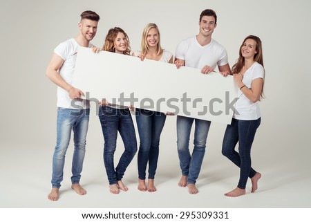 Full Length Shot of Happy Young Friends in Casual Clothing, Holding White Rectangular Board with Copy Space Against Off-White Background Inside the Studio. - stock photo