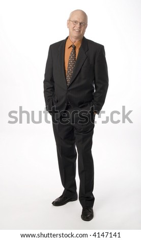 full length shot of man dressed in suit standing with hands in pockets - stock photo