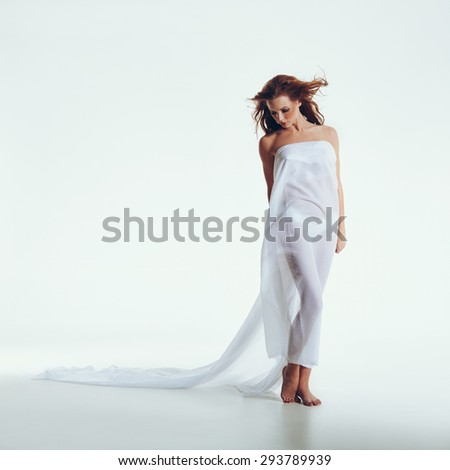 Full length shot of nude woman covered with transparent textile. Naked brunette posing on white background with lots of copyspace. - stock photo