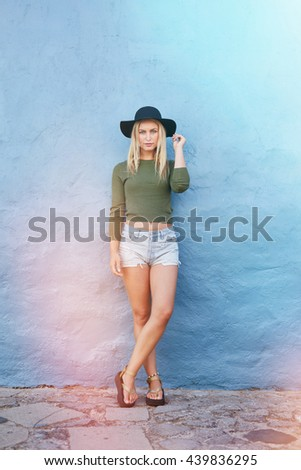 Full length shot of trendy young female model standing against blue wall and looking at camera. Fashionable young woman in casuals and hat. - stock photo