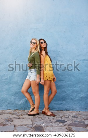 Full length shot of two beautiful women in stylish casuals posing outside against blue wall. Street style fashion. - stock photo