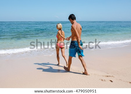 Full length shot of young couple going for swim in sea. Woman holding hand of her boyfriend while walking on the sea shore. Couple enjoying honeymoon on a tropical beach.