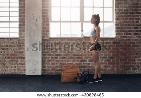 Full length shot of young female standing at gym and looking away. Woman in sportswear standing at the fitness club with kettlebell on floor. - stock photo