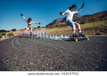 Full length shot of young man and woman outdoors longboarding down the road. Skate boards with smoke grenade. People practicing skating on rural road. - stock photo