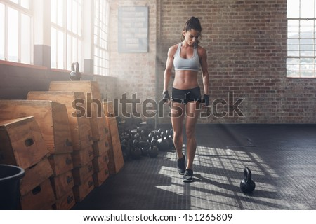 Full length shot of young woman in sportswear taking a walk in the cross fit gym and looking at kettle bell on floor. Fitness female getting ready for intense crossfit workout. - stock photo