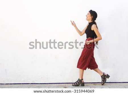 Full length side portrait of a smiling teen walking and looking at mobile phone  - stock photo