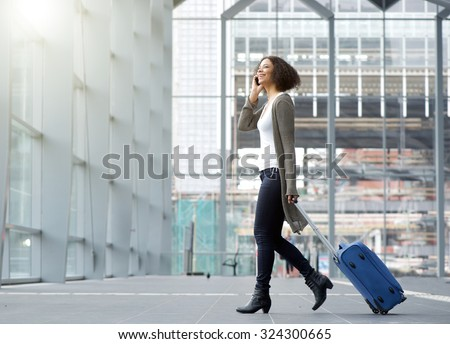 Full length side portrait of a traveling young woman with mobile phone and suitcase - stock photo