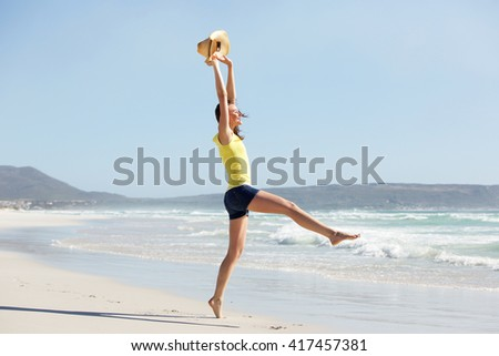Full length side portrait of excited young woman enjoying holiday at the beach  - stock photo