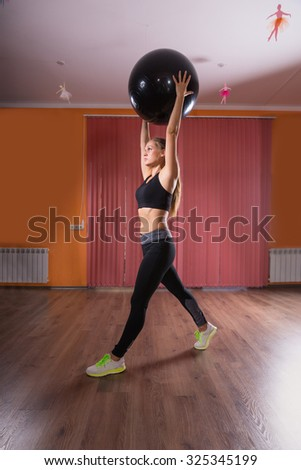 Full Length Side Profile of Healthy Young Woman Stretching with Inflatable Exercise Ball Held Over Head in Dance Studio with Hardwood Floor