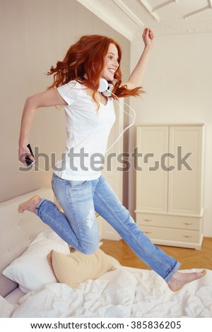 Full Length Side Profile of Young Woman with Long Red Hair Leaping in Air While Jumping on Bed and Listening to Music on Cell Phone Player with Headphones in Luxury Bedroom - stock photo