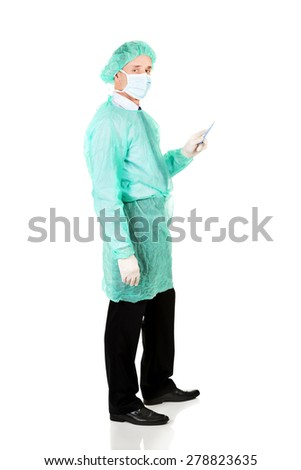 Full length side view male doctor with a scalpel. - stock photo