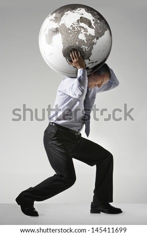 Full length side view of a businessman struggling to carry globe on shoulders against gray background - stock photo