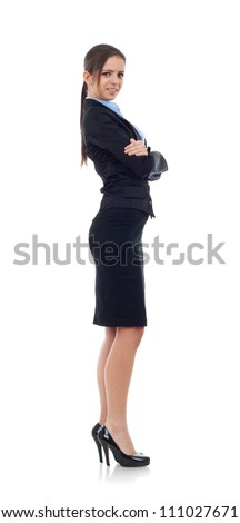 Full length, side view of a confident young business woman standing with crossed hands isolated over white background